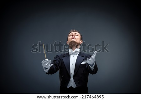 Emotional conductor in a tuxedo on a dark background - stock photo