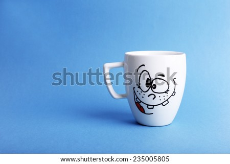 Emotional cup on blue background - stock photo