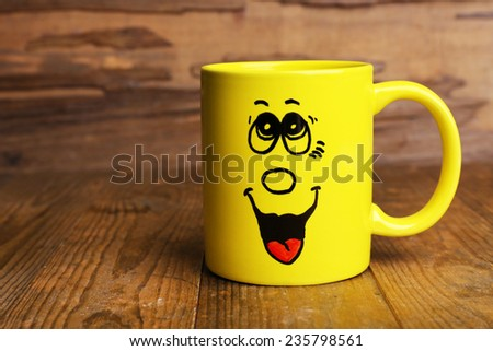 Emotional cup on wooden background - stock photo