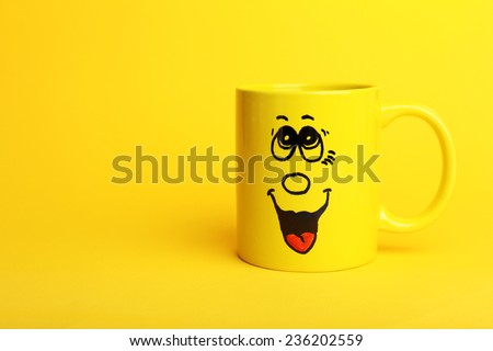 Emotional cup on yellow background - stock photo
