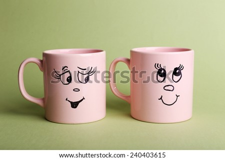 Emotional cups on green background - stock photo