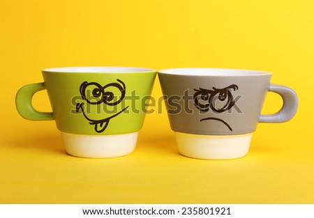 Emotional cups on yellow background - stock photo