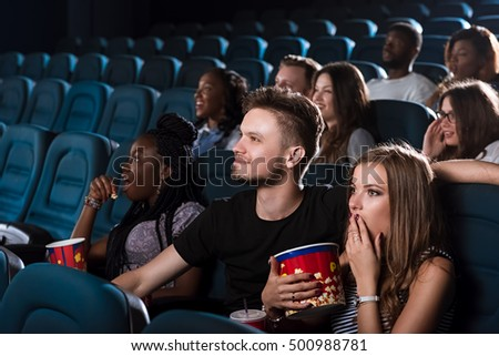 Emotional date. Beautiful young woman looking shocked while watching a movie with her boyfriend at the cinema