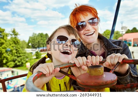 emotional daughter and mother in sunglasses in the amusement park. child and mommy outdoors. vacation in the summer park