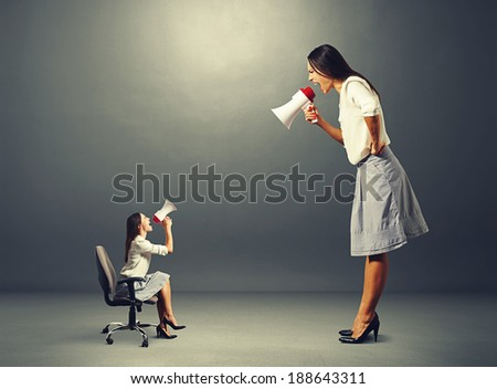 emotional displeased women with megaphone over dark background - stock photo