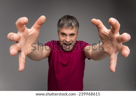 Emotional facial expression of man - scary. scary looking man reaching forward to grab someone - stock photo