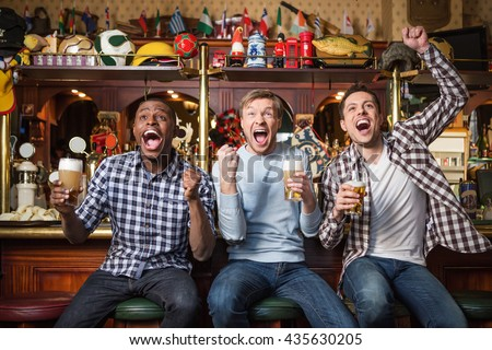 Emotional fans with a beer at a bar - stock photo