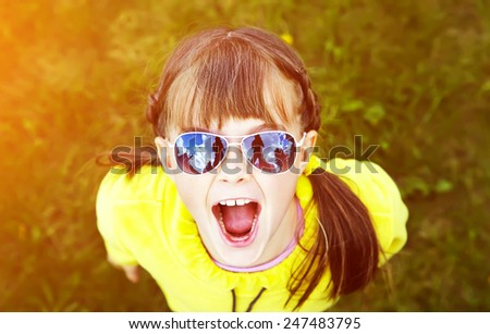 emotional girl in sunglasses in the park. children outdoors. vacation in the summer park - stock photo