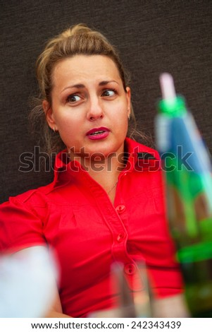 Emotional girl in the restaurant, stopped in surprise - stock photo