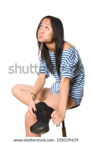 Emotional girl with compressed lips looks upward.Asian girl is isolated on a white background - stock photo