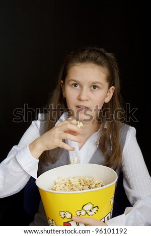 emotional girl with popcorn on a black background - stock photo