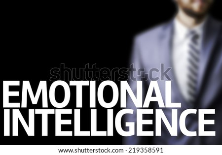 Emotional Intelligence written on a board with a business man on background - stock photo