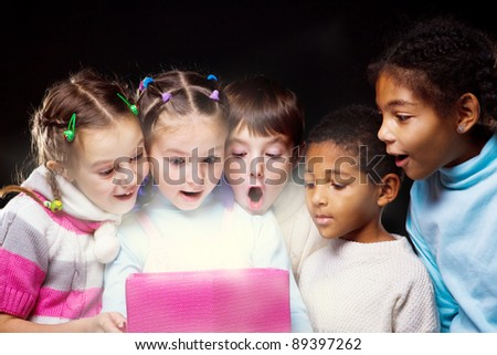 Emotional kids looking inside the shining present box - stock photo
