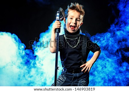 Emotional little boy is singing into a microphone like a rock musician.  - stock photo