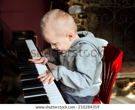 Emotional little boy learning to diligently play on the piano - stock photo