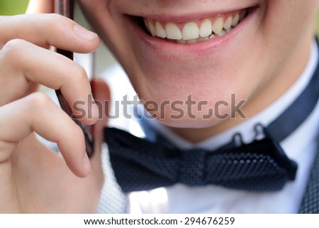 Emotional male with beautiful clear white open mouth smile of young boy with clean healthy teeth in formal clothes with bow tie speaking by phone closeup, horizontal picture - stock photo