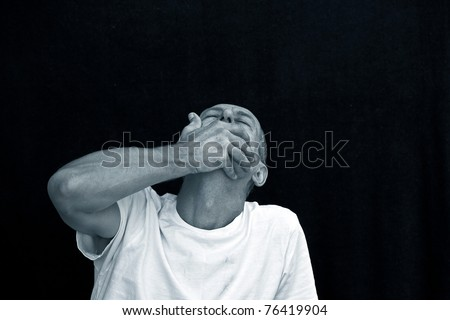emotional man cowering in grief against black background - stock photo