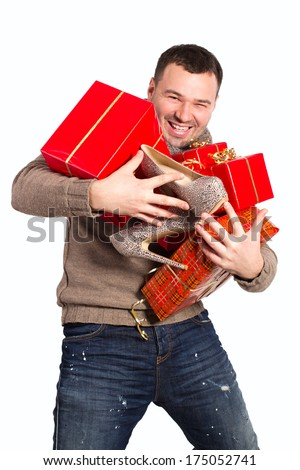 Emotional man holding a lot of gifts in his hands. Man bought a lot of gifts for the woman he loved. Women's shoes as a gift in the hands of men. Gifts in red packing for a holiday falls from hands.