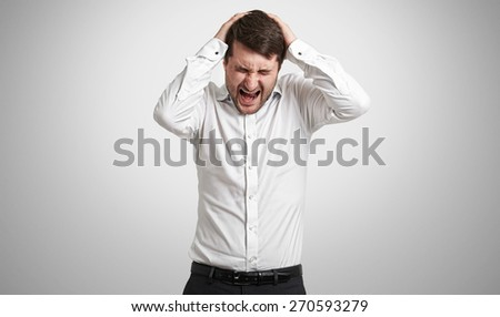 emotional man in white shirt holding his head and screaming in pain over light grey background - stock photo