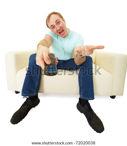 emotional man with a TV remote control sitting on the couch - stock photo