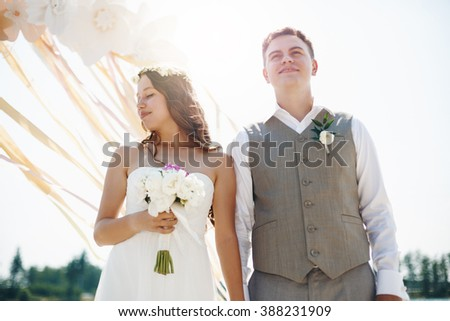 Emotional Moment of Wedding Ceremony. Beautiful Newlywed Couple. Groom and Bride Outdoors in Sun Light. Selective Focus. - stock photo