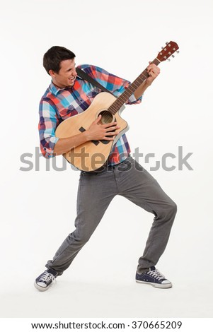 Emotional musician playing his guitar. Artistic guy with guitar. Young musician singing emotional and playing guitar.