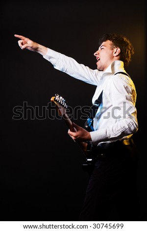 emotional musician with guitar pointing - stock photo