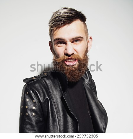 Emotional portrait of a bearded young man in a leather jacket in the studio