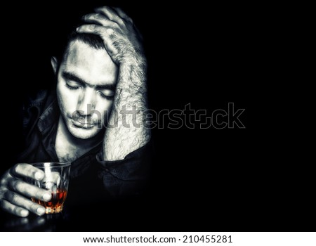 Emotional portrait of a drunk man holding a glass of whisky on a black background - stock photo