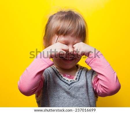 Emotional portrait of a girl crying and hiding her face - stock photo