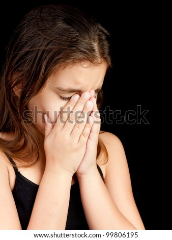 Emotional portrait of a girl crying and hiding her face isolated on black with space for text - stock photo