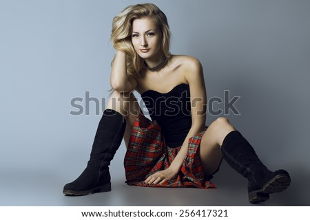 Emotional portrait of a gorgeous fashion blond model  posing over grey background, sitting on the floor.  Studio shot. Hipster style. Copy space - stock photo