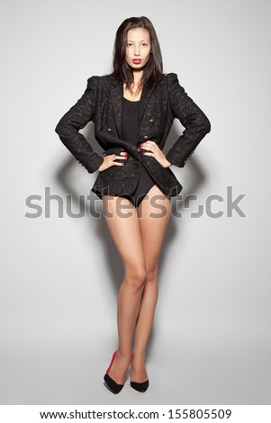 Emotional portrait of a gorgeous fashion model posing in black jacket and body shirt over gray background. Studio shot - stock photo