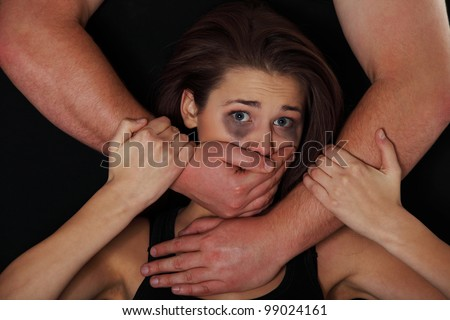 Emotional portrait of abused woman isolated on black - stock photo