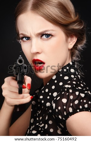 Emotional portrait of beautiful young angry blond woman with revolver in hand - stock photo
