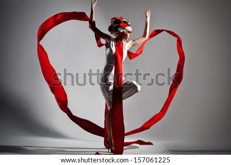 emotional portrait of fashion woman in exclusive dress posing in studio, making heart from textile in motion - stock photo