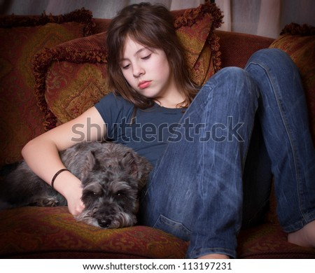 Emotional portrait of looking alone and sad with her dog on couch - stock photo