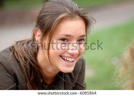 emotional portrait of  young woman in park on  green background