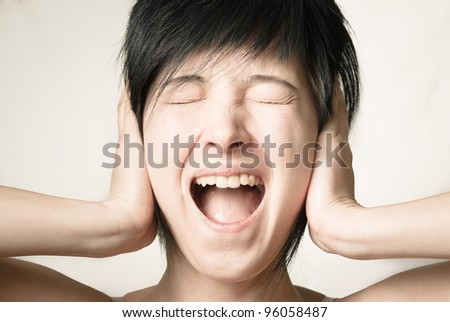 Emotional scream. Young woman shouting and covered her ears with her hands, front view