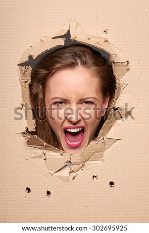 Emotional screaming girl peeping through hole in paper - stock photo