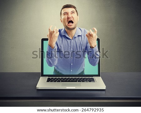 emotional screaming man got out of the laptop against dark background - stock photo