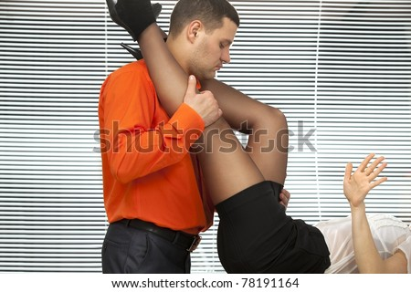 Emotional sexy scene -  strong young man embracing woman's perfect legs on the desk in office - stock photo