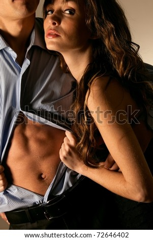 Emotional sexy scene young woman undressing her partner - stock photo