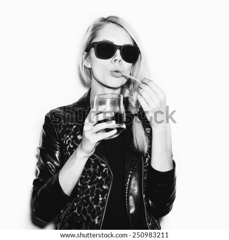 Emotional sexy woman in sunglasses drinking alcohol cocktail. Toned. White background, not isolated - stock photo
