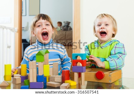 Emotional sibling playing in toy blocks in home interior - stock photo