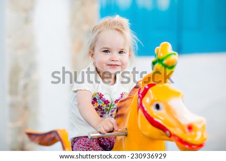Emotional smiling little girl riding on the carousel - stock photo