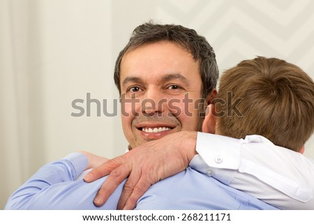 Emotional tight hug of father and son. Sincere love of parent and child - stock photo