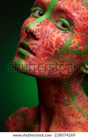emotional woman with red multi lines and green hair. red flowers face art and body paint - stock photo
