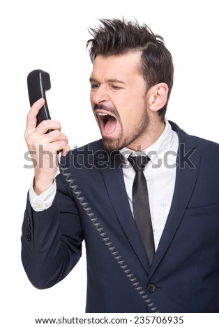 Emotional young man is screaming on the phone. The human face, expression, emotion, body language. - stock photo
