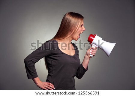emotional young woman shouting in loudspeaker - stock photo